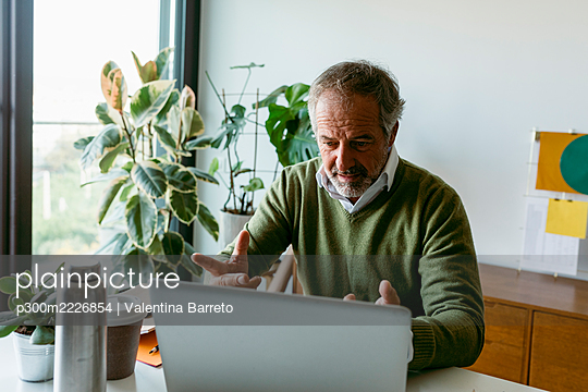 Mature man doing video call on laptop while sitting at home - p300m2226854 by Valentina Barreto