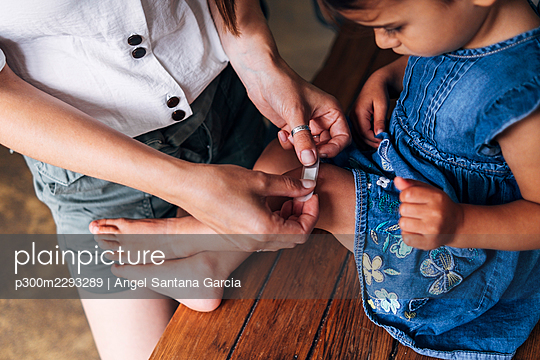 Mother putting bandage on daughter's knee at home - p300m2293289 by Angel Santana Garcia