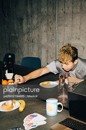 Man eating candy at table in office - p426m2194685 by Maskot