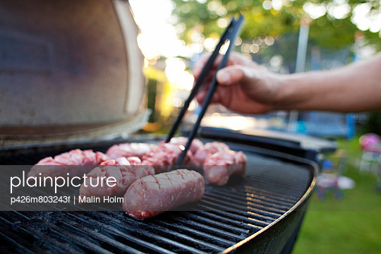 Man's hand grilling meat on barbecue in yard - p426m803243f by Malin Holm