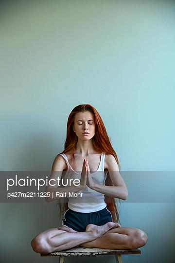 Rothaarige Frau im Lotossitz beim Yoga - p427m2211225 von Ralf Mohr