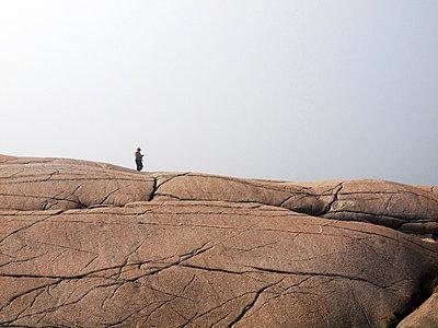 Person at Peggys Cove in Nova Scotia - p1072m828960 by Clive Branson