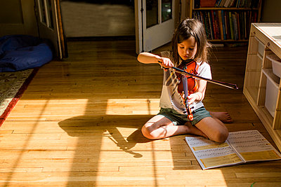 A small girl sits on floor playing violin in front of open music book - p1166m2171954 by Cavan Images