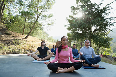 Serene people meditating in lotus position on deck - p1192m1157986 by Hero Images