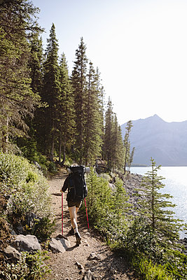 Female backpacker hiking on trail along sunny lakeside - p1192m2129253 by Hero Images
