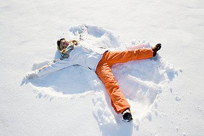 teenage girl making snow angel - p3163063f by Lea Roth photography