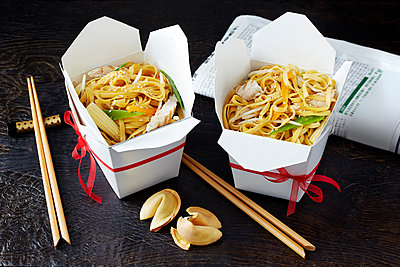 Still life with chinese noodles in takeaway boxes, asian takeaway food - p429m2068560 by Danielle Wood