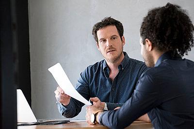 Men discussing document - p623m1506891 by Eric Audras