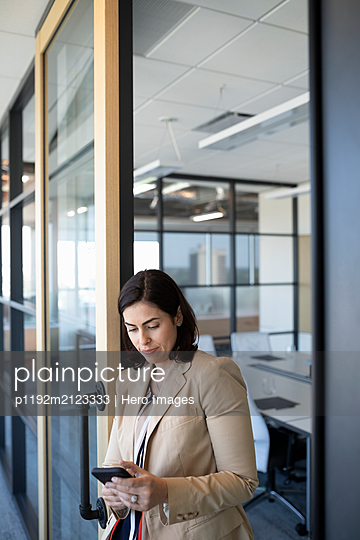 Businesswoman using cell phone outside meeting room - p1192m2123333 by Hero Images