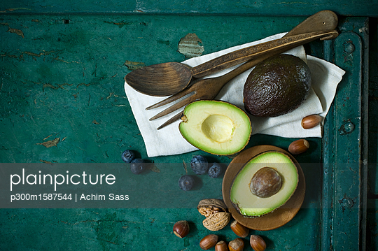 Cloth, salad cutlery, avocados, blueberries and nuts on green ground - p300m1587544 von Achim Sass