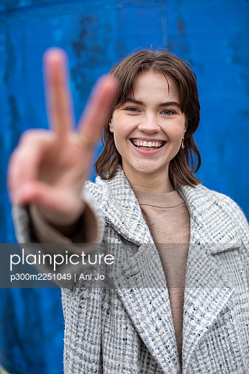 Smiling female showing peace gesture against blue wall - p300m2251049 by Ani Jo