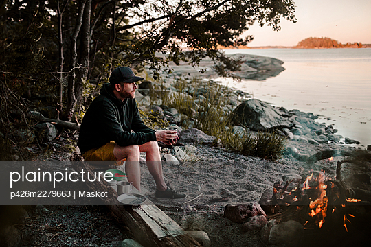 Full length of man looking away while sitting on log by campfire at lakeshore - p426m2279663 by Maskot