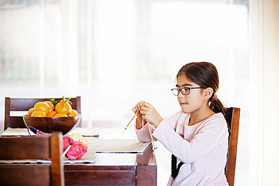 Girl knitting while sitting at table - p1166m1209343 by Cavan Images