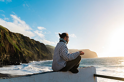 Man meditating at the coast at sunset, Sao Miguel Island, Azores, Portugal - p300m2169969 by VITTA GALLERY