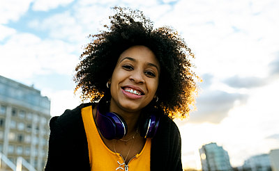 Smiling young woman with afro hair against sky during sunset - p300m2243850 by Marco Govel