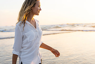 Smiling woman looking away while standing against sea during sunset - p300m2244071 by Steve Brookland