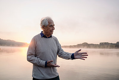 Senior man gesturing while standing against lake during sunrise - p300m2252213 by Gustafsson