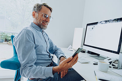 Mature businessman using smart phone while sitting at home office - p300m2266726 by Mareen Fischinger