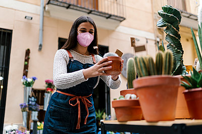 Young female florist with protective face mask holding potted plant at store - p300m2274925 by Ezequiel Giménez