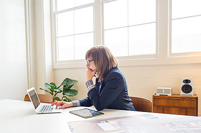 Businesswoman using laptop at desk in office - p555m1409653 by Shestock