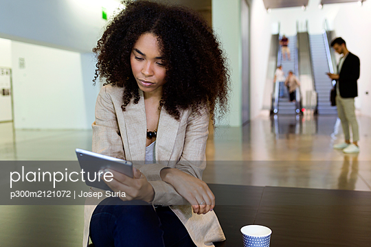 Young businesswoman with takeaway coffee using tablet in a foyer - p300m2121072 by Josep Suria