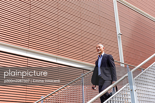 Male professional moving down from staircase - p300m2287337 by Emma Innocenti