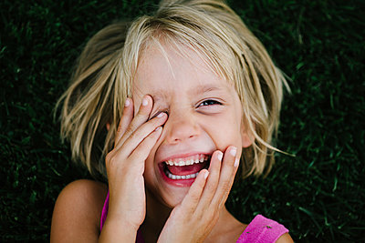 Overhead portrait of happy girl rubbing eye while lying on grass - p1166m1474447 by Cavan Images