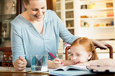 Mid adult mother helping daughter with school homework at dining room table - p1427m2283159 by Roberto Westbrook