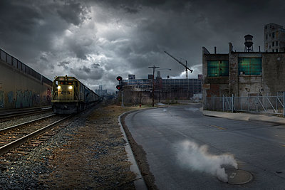 Train on train tracks in dilapidated industrial city - p555m1411140 by Chris Clor