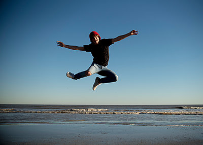 Happy teenage boy jumping on the beaches of Galveston, Texas. - p1166m2073505 by Cavan Images