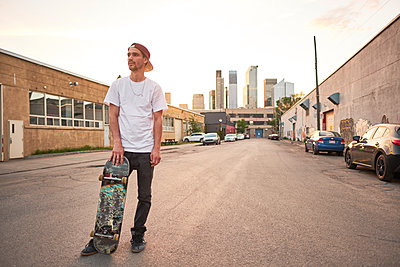 Young skateboarder standing in street in industrial urban area during sunset, Montreal, Quebec, Canada - p1362m1530064 by Charles Knox