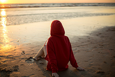 Young woman wearing red hooded jacket sitting on the beach at sunset - p300m2029366 von Jean Schwarz