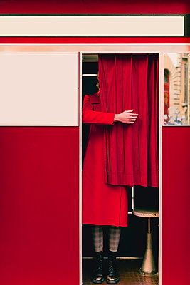 Woman wearing red coat and boots standing behind curtain in a photo booth - p300m2170160 by Francesco Morandini