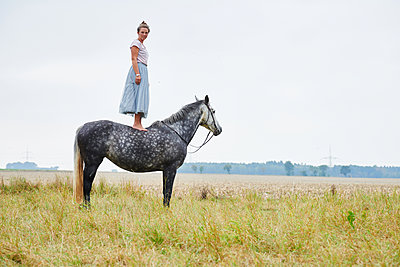Woman in skirt standing on top of dapple grey horse in field - p429m1407710 by Conny Marshaus
