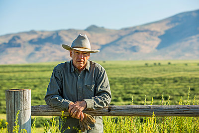 Caucasian farmer holding gloves leaning on wooden fence - p555m1303713 by Steve Smith