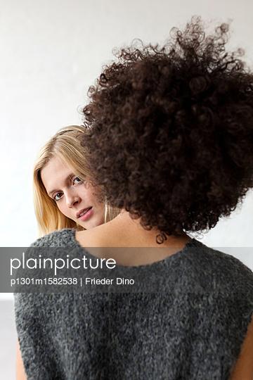 Blonde Frau hinter einer Frau mit Afrolook - p1301m1582538 von Delia Baum