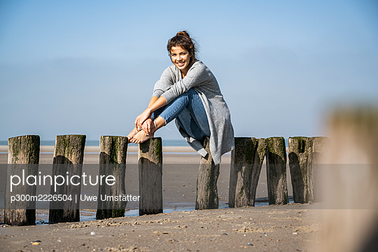 Smiling young woman sitting on wooden posts at beach against sky during sunny day - p300m2226504 by Uwe Umstätter