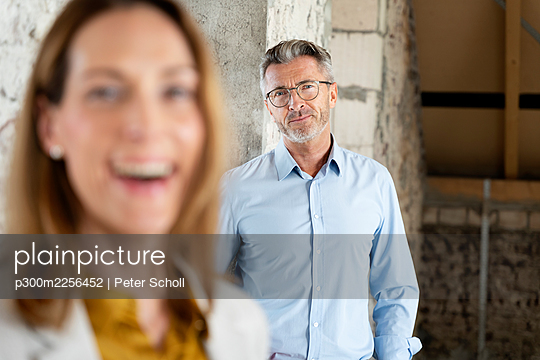 Mature architect staring while standing with businesswoman at construction site - p300m2256452 by Peter Scholl