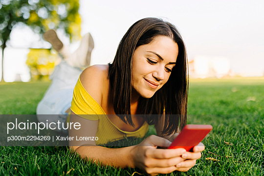 Young woman using mobile phone while lying in public park - p300m2294269 by Xavier Lorenzo