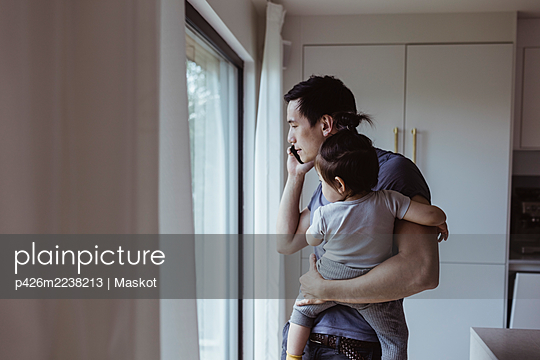 Father talking on mobile phone while carrying son at home - p426m2238213 by Maskot