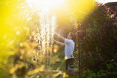 Man adjusting sprinkler in sunny summer garden - p1023m2262012 by Martin Barraud