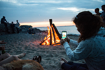 Woman taking photographs of campfire on beach - p1142m1362242 by Runar Lind