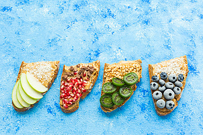 Row of bread slices with various toppings - p300m2060298 by JLPfeifer