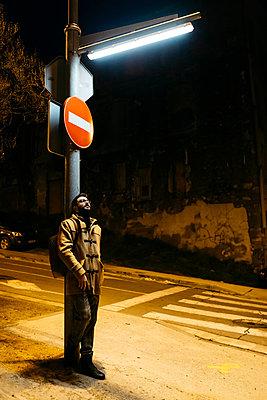 Spain, Igualada, man standing under a street lamp at night - p300m2080527 von Josep Rovirosa