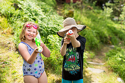 Brother and sister playing with water guns - p312m1211257 by Susanne Kronholm