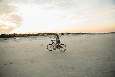 Caucasian girl riding bicycle on beach - p555m1522773 by Marc Romanelli
