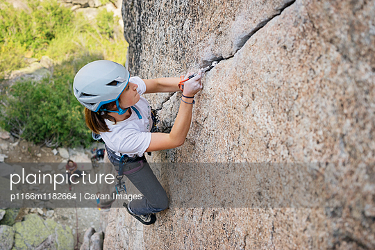 High angle view of confident woman climbing mountain - p1166m1182664 by Cavan Images
