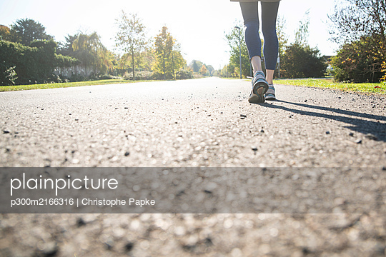 Close-up of running woman on footpath - p300m2166316 by Christophe Papke