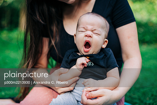 Tired baby boy yawning while sitting with mother at park during weekend - p300m2213930 by Alexandra C. Ribeiro