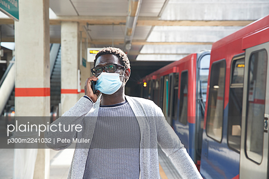 Male entrepreneur wearing protective face mask while talking on mobile phone at railroad station - p300m2241032 by Pete Muller